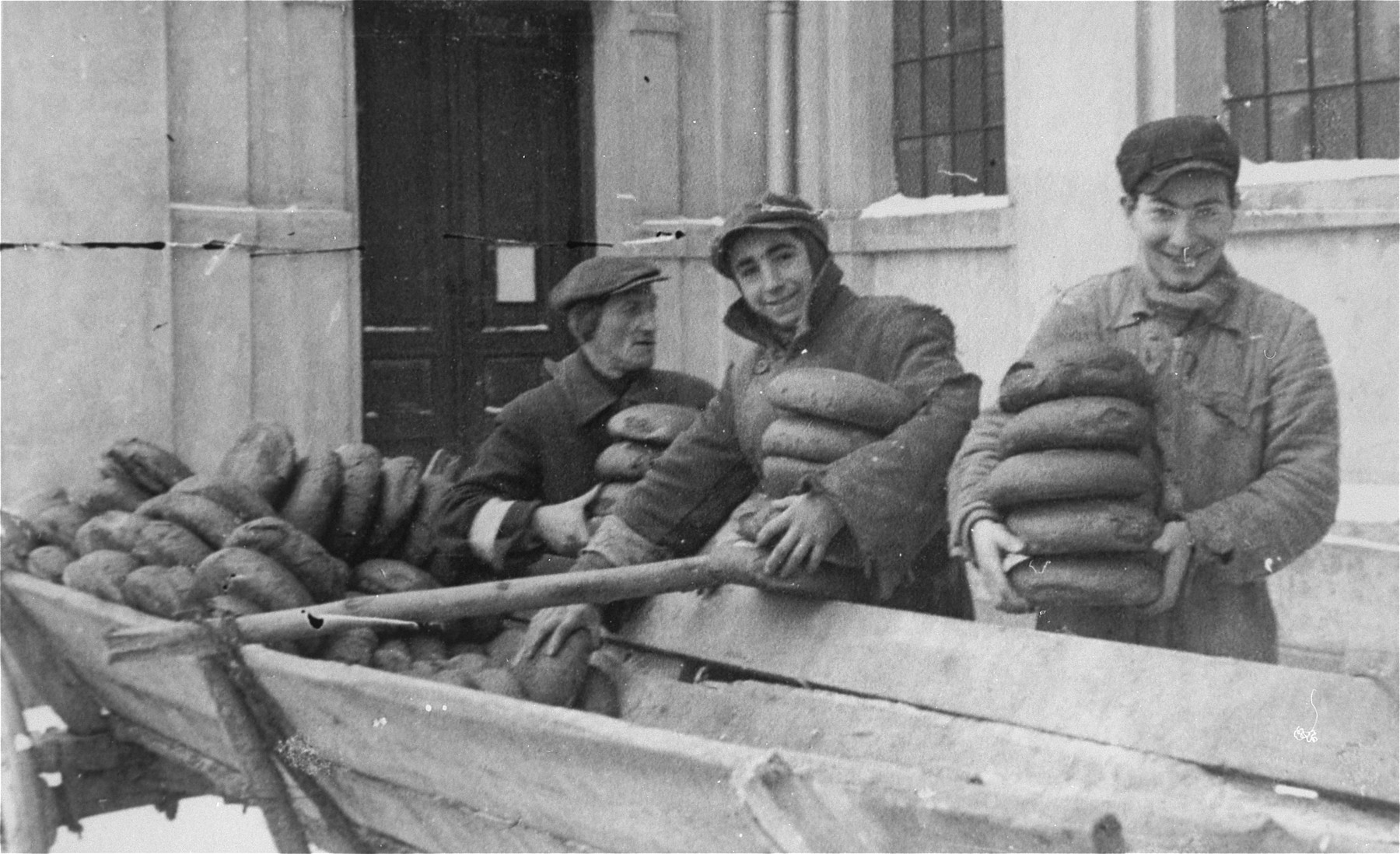 Jewish men and youths remove loaves of bread from a wagon at the soup kitchen in the Kielce ghetto.  This photo was one the images included in an official album prepared by the Judenrat of the Kielce ghetto in 1942.