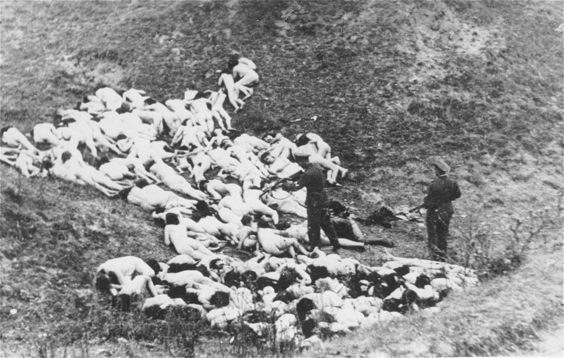 A German police officer shoots Jewish women still alive after a mass execution of Jews from the Mizocz ghetto.  According to the Zentrale Stelle in Germany (Zst. II 204 AR 1218/70), these Jews were collected by the German Gendarmerie and Ukrainian Schutzmannschaft during the liquidation of the Mizocz ghetto, which held roughly 1,700 Jews.  On the eve of the ghetto's liquidation (13 October 1942), some of the inhabitants rose up against the Germans and were defeated after a short battle.  The remaining members of the community were transported from the ghetto to this ravine in the Sdolbunov Gebietskommissariat, south of Rovno, where they were executed.  Information regarding this action, including the photos, were acquired from a man named Hille, who was the Bezirks-Oberwachtmeister of the Gendarmerie at the time.  Hille apparently gave the five photos (there were originally seven) to the company lawyer of a textile firm in Kunert, Czechoslovakia, where he worked as a doorman after the war.  The Czech government confiscated the photos from the lawyer in 1946 and they subsequently became public.  That the photos indeed show the shooting of Jews in connection with the liquidation of the ghetto was also confirmed by a statement of Gendarmerie-Gebietsfuehrer Josef Paur in 1961.