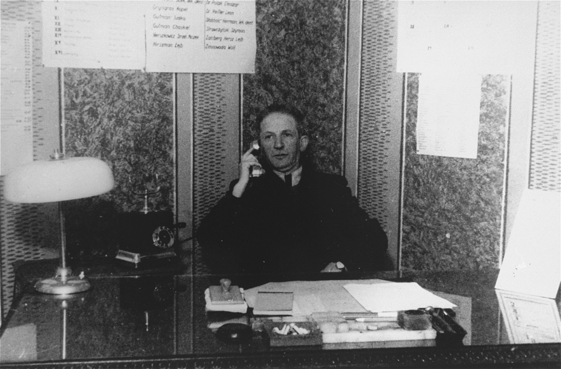 A member of the ghetto administration talks on the telephone while seated at his desk in the office of the Judenrat in the Kielce ghetto.  This photo was one the images included in an official album prepared by the Judenrat of the Kielce ghetto in 1942.