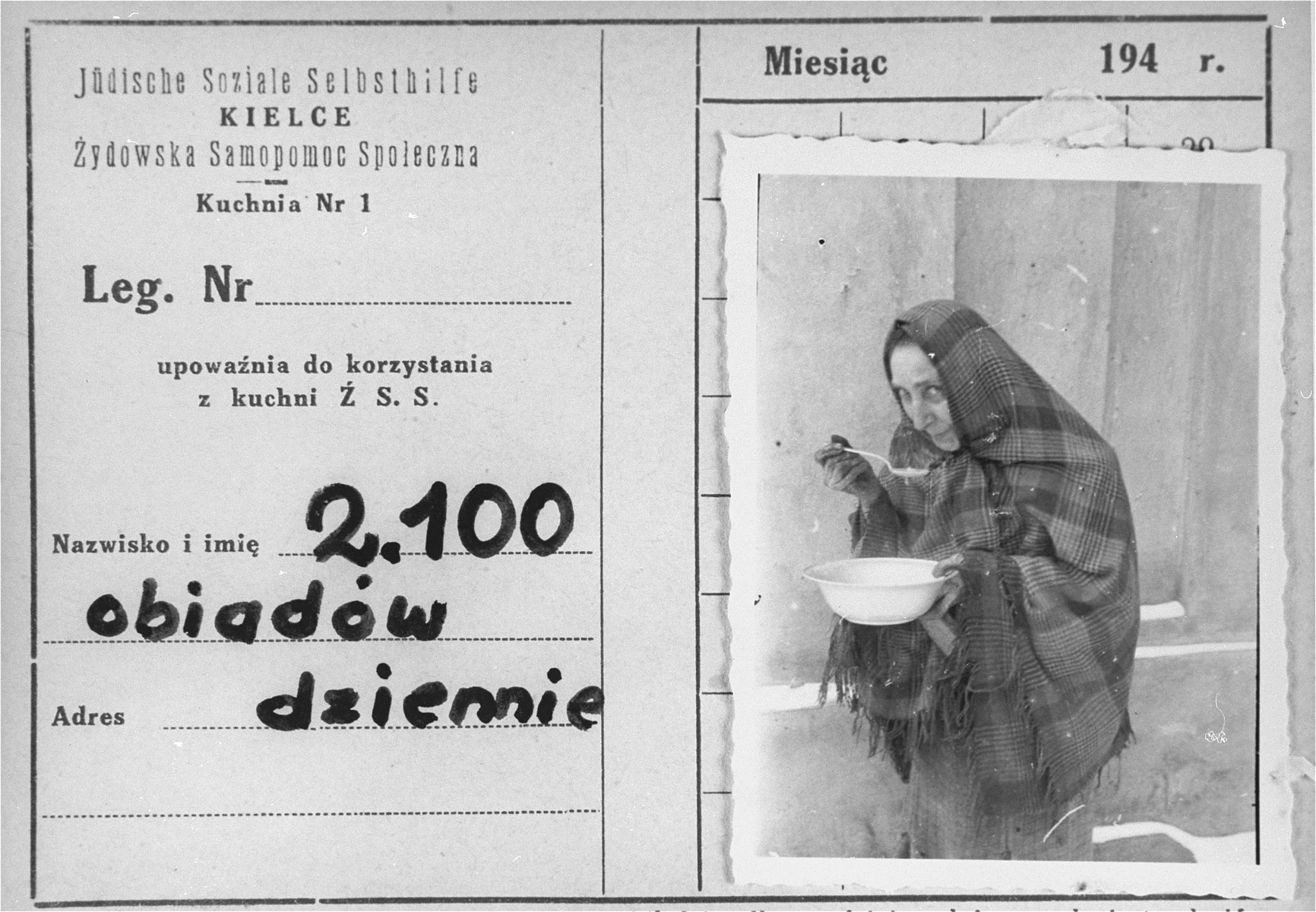 An identification card bearing a photo of a woman eating a bowl of soup in the Kielce ghetto.  An official ID card was required to receive food rations at the soup kitchen organized by the Jewish Social Self-help Committee of the Jewish Council. The inscription in Polish reads: 2,100 dinners served daily.  This photo was one the images included in an official album prepared by the Judenrat of the Kielce ghetto in 1942.