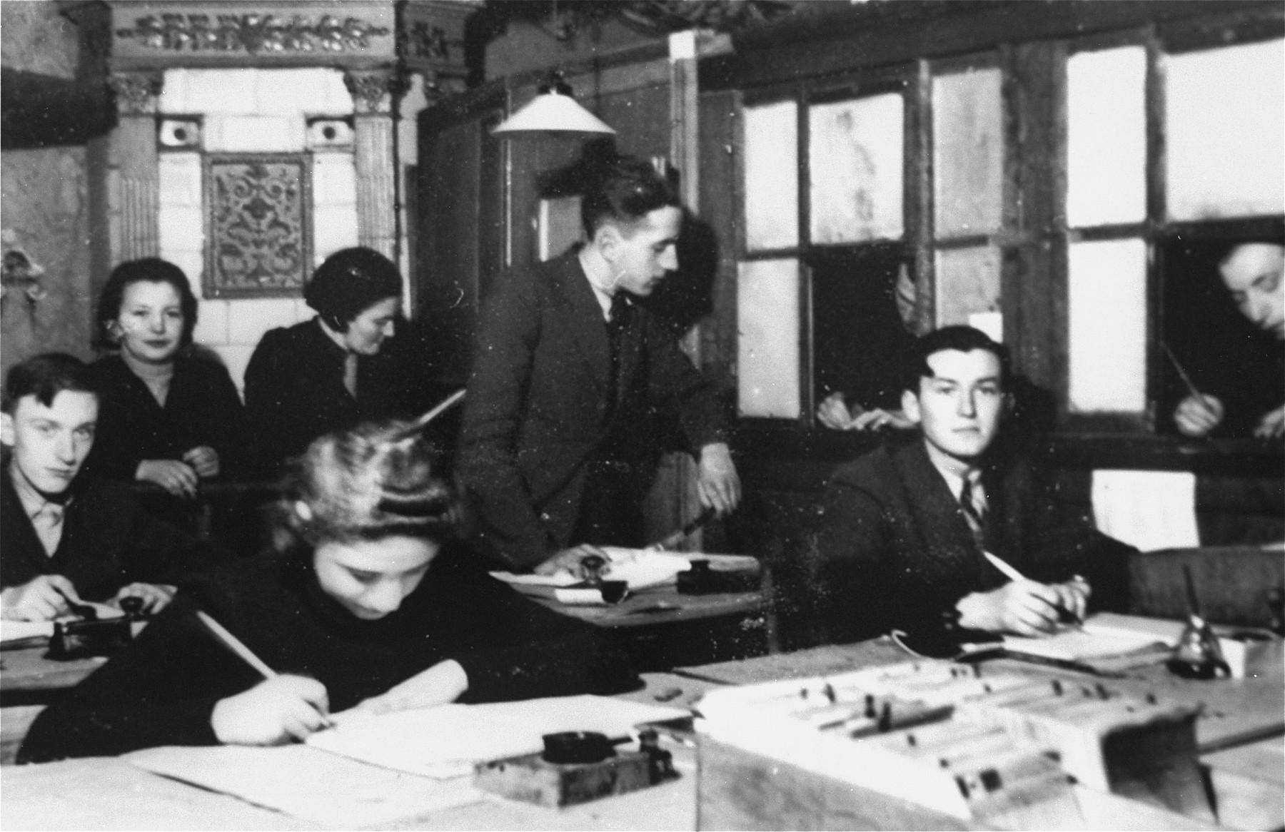 Members of the ghetto administration at work in the office of the Judenrat in the Kielce ghetto.  This photo was one the images included in an official album prepared by the Judenrat of the Kielce ghetto in 1942.
