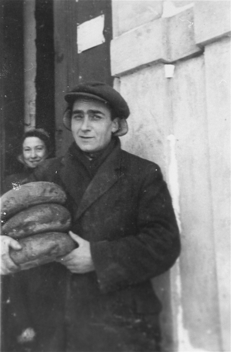 A Jewish man brings loaves of bread to the soup kitchen in the Kielce ghetto.