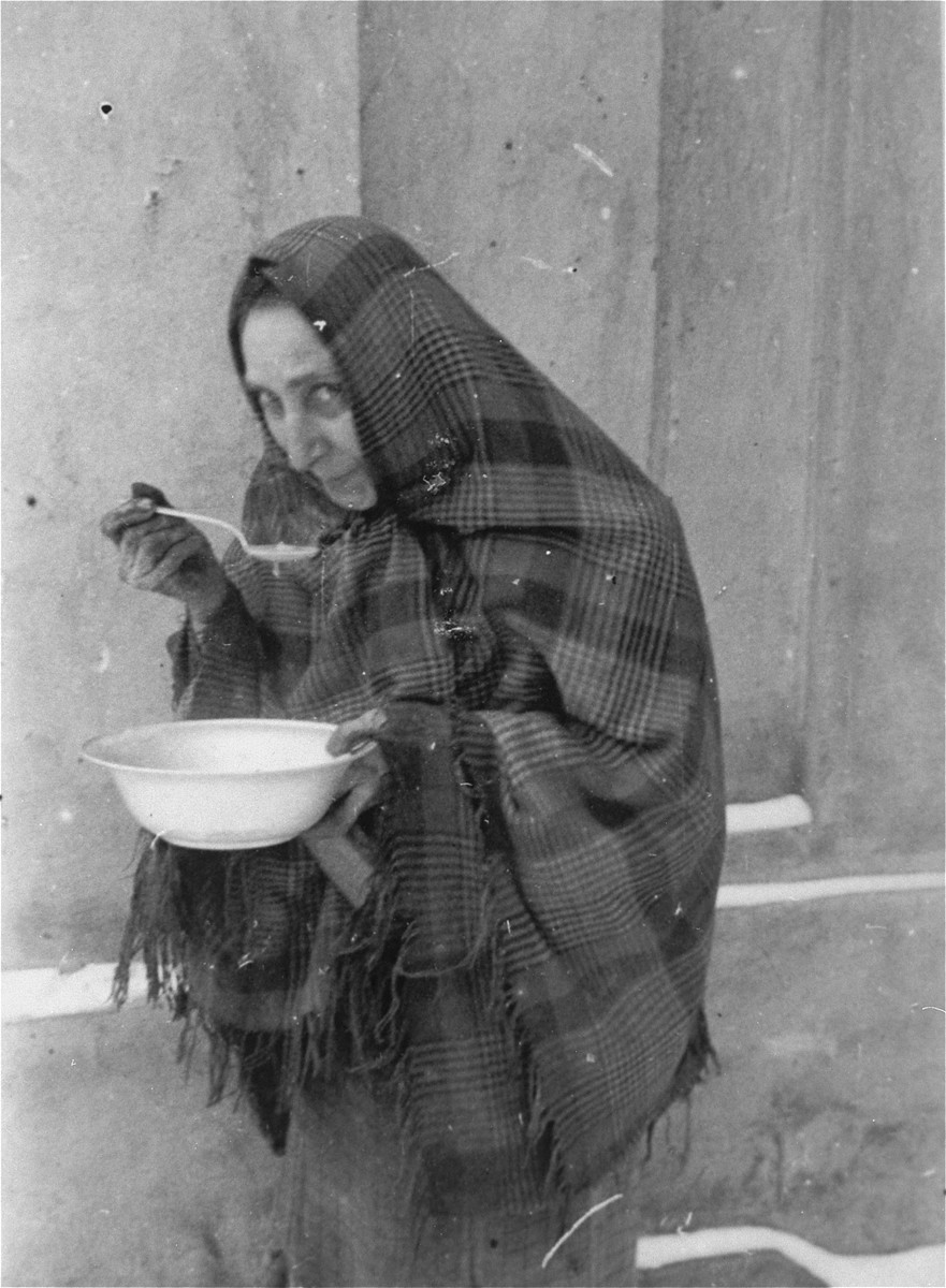 A Jewish woman eats a bowl of soup that she received at the public kitchen in the Kielce ghetto.    This photo was one the images included in an official album prepared by the Judenrat of the Kielce ghetto in 1942.