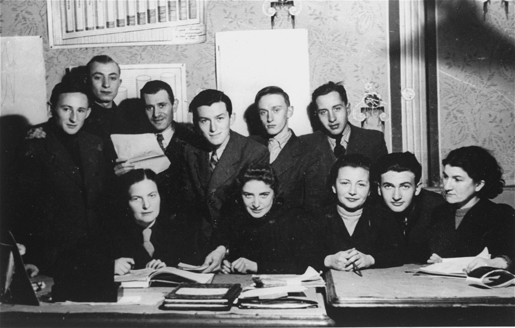 Group portrait of members of the administrative staff of the Kielce ghetto Judenrat (Jewish Council) in their office.  This photo was one the images included in an official album prepared by the Judenrat of the Kielce ghetto in 1942.