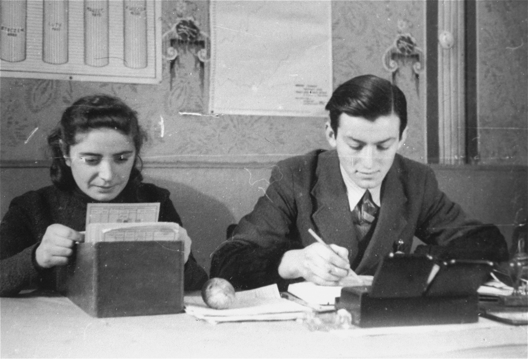 Two members of the ghetto administration at work in the office of the Judenrat in the Kielce ghetto.  This photo was one the images included in an official album prepared by the Judenrat of the Kielce ghetto in 1942.