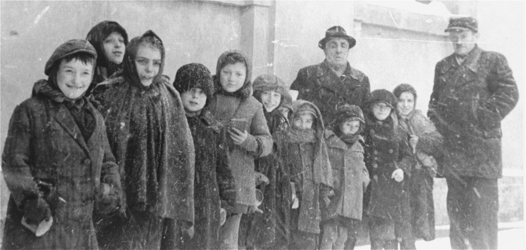 Group portrait of children from a Kielce ghetto orphanage standing on the street.  This photo was one the images included in an official album prepared by the Judenrat of the Kielce ghetto in 1942.