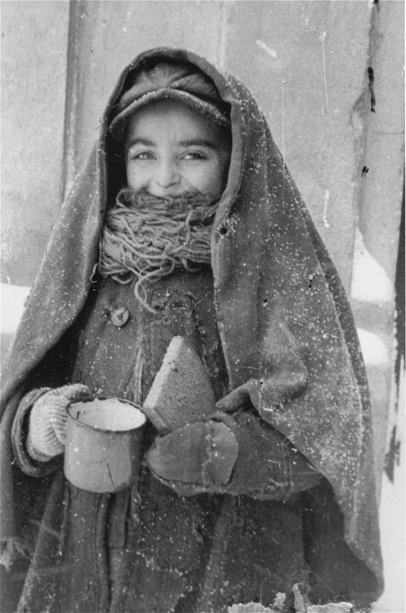 A Jewish child wearing a blanket, holds a cup and a piece of bread in the Kielce ghetto.
