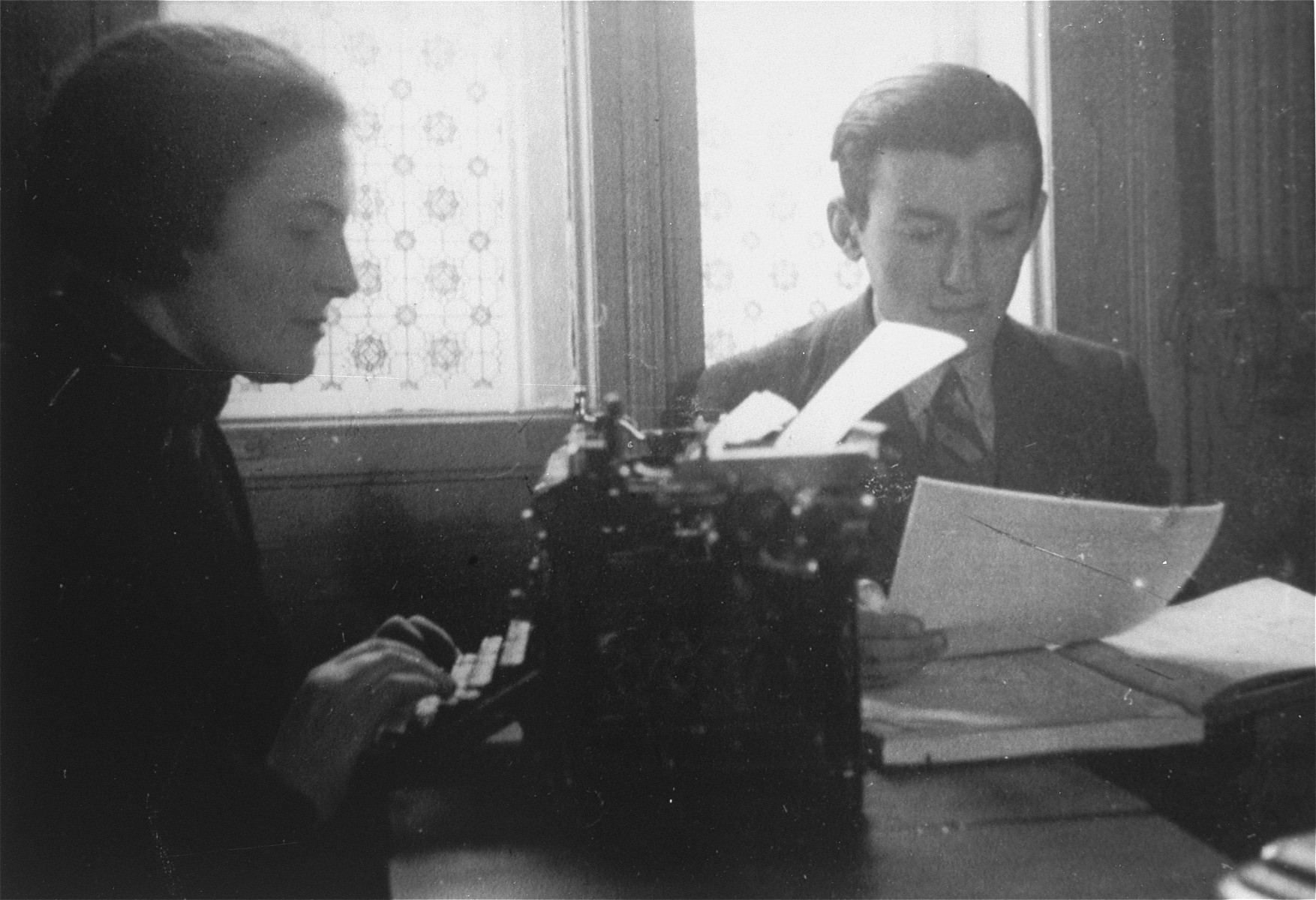 Two members of the ghetto administration sit at a desk in the office of the Judenrat in the Kielce ghetto.  This photo was one the images included in an official album prepared by the Judenrat of the Kielce ghetto in 1942.