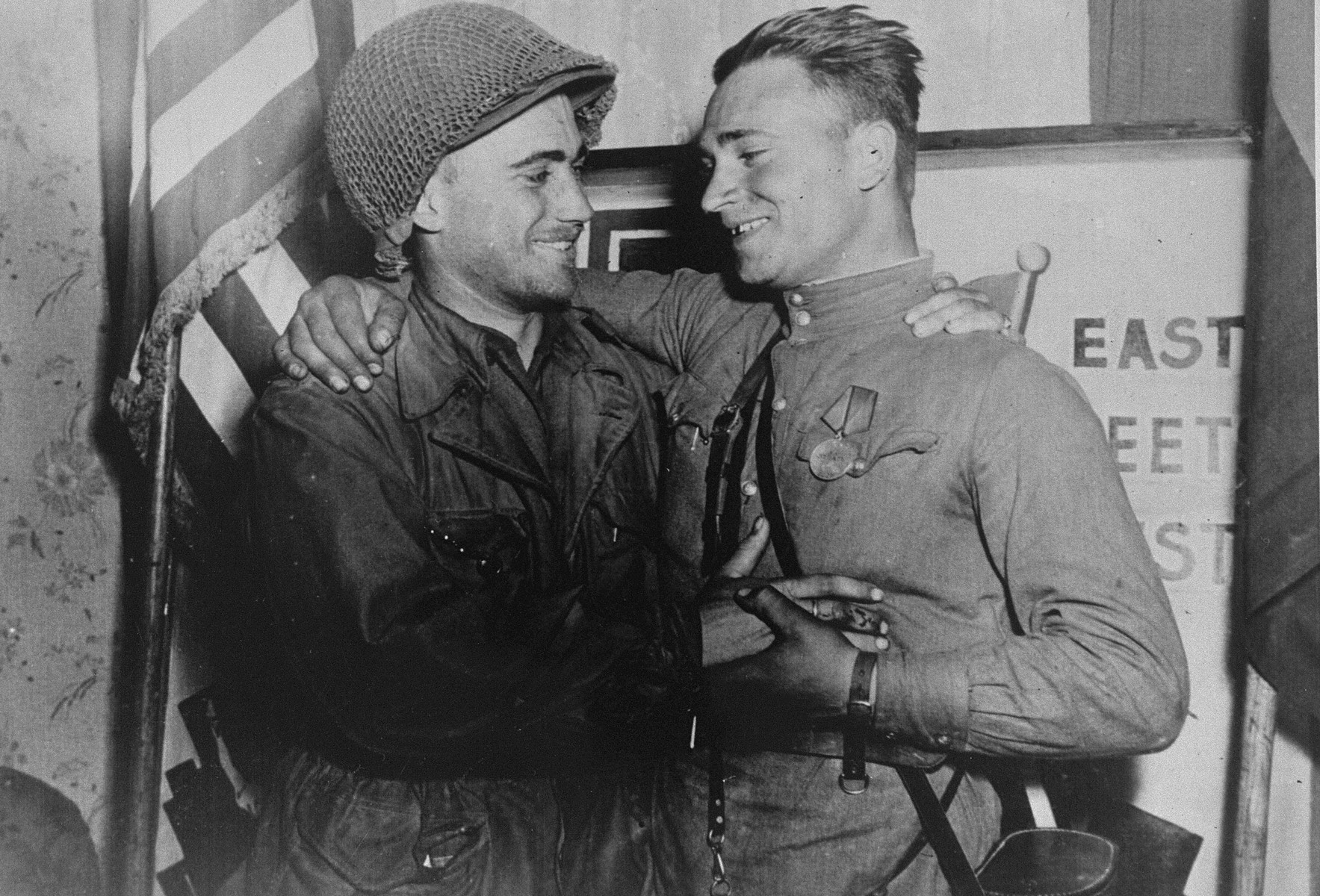 """U.S. 2nd Lt. William Robertson and Russian Lt. Alexander Sylashko embrace in front of sign that reads, """"East Meets West,"""" after the American and Soviet armies linked up near Torgau, Germany."""