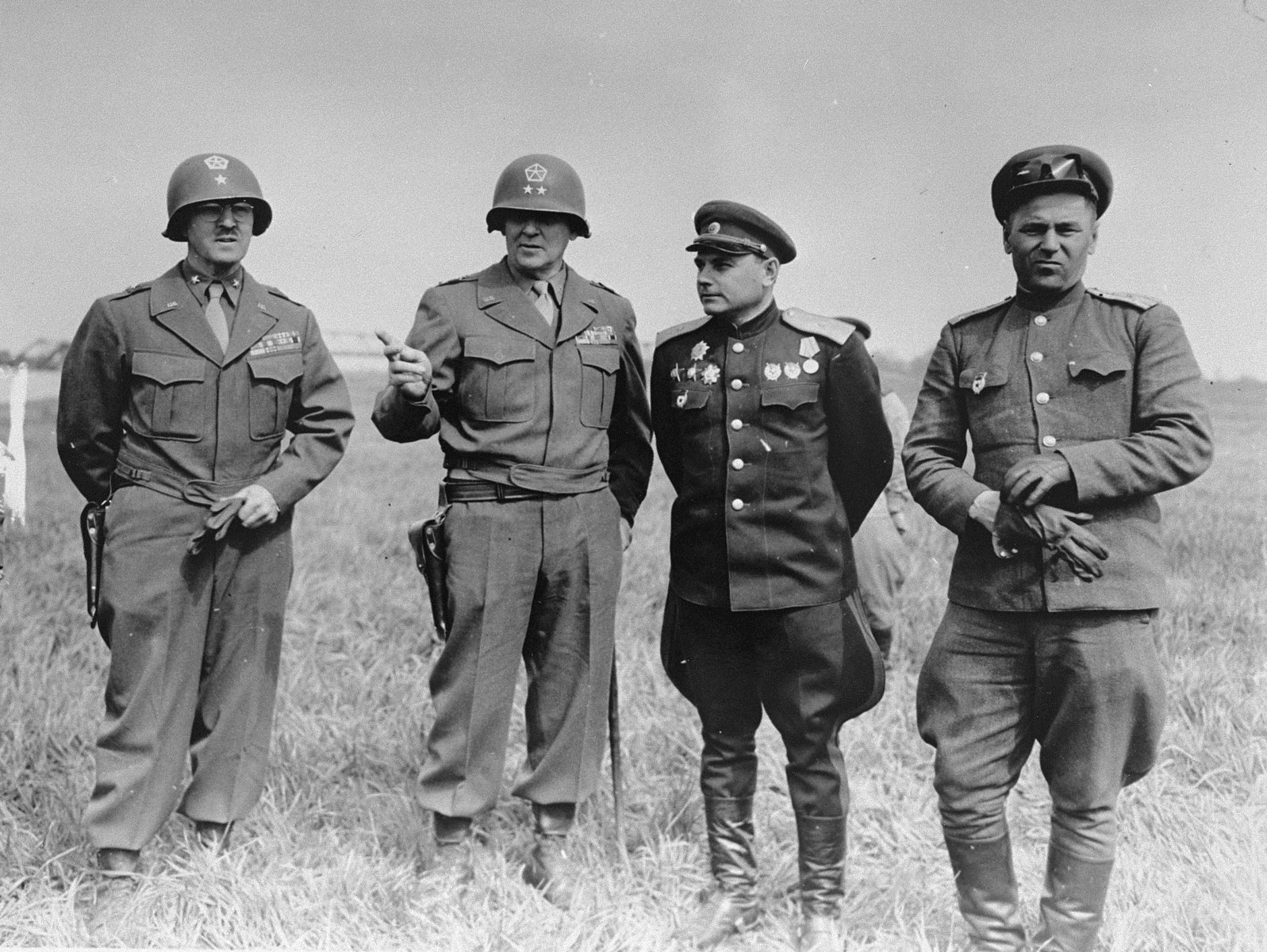 American and Soviet generals pose on the banks of the Elbe River near Torgau, Germany, where the two Allies linked up for the first time.  Pictured from left to right are Brig. Gen. Charles G. Helmick (Artillery General of V Corps), Maj. Gen. Clarence R. Huebner (CG V Corps, First U.S. Army), Lt. Gen. Baclanow (Commanding General Russian 34th Corps), and Maj. Gen. Rusacov (Commanding General Russian 58th Infantry Div).
