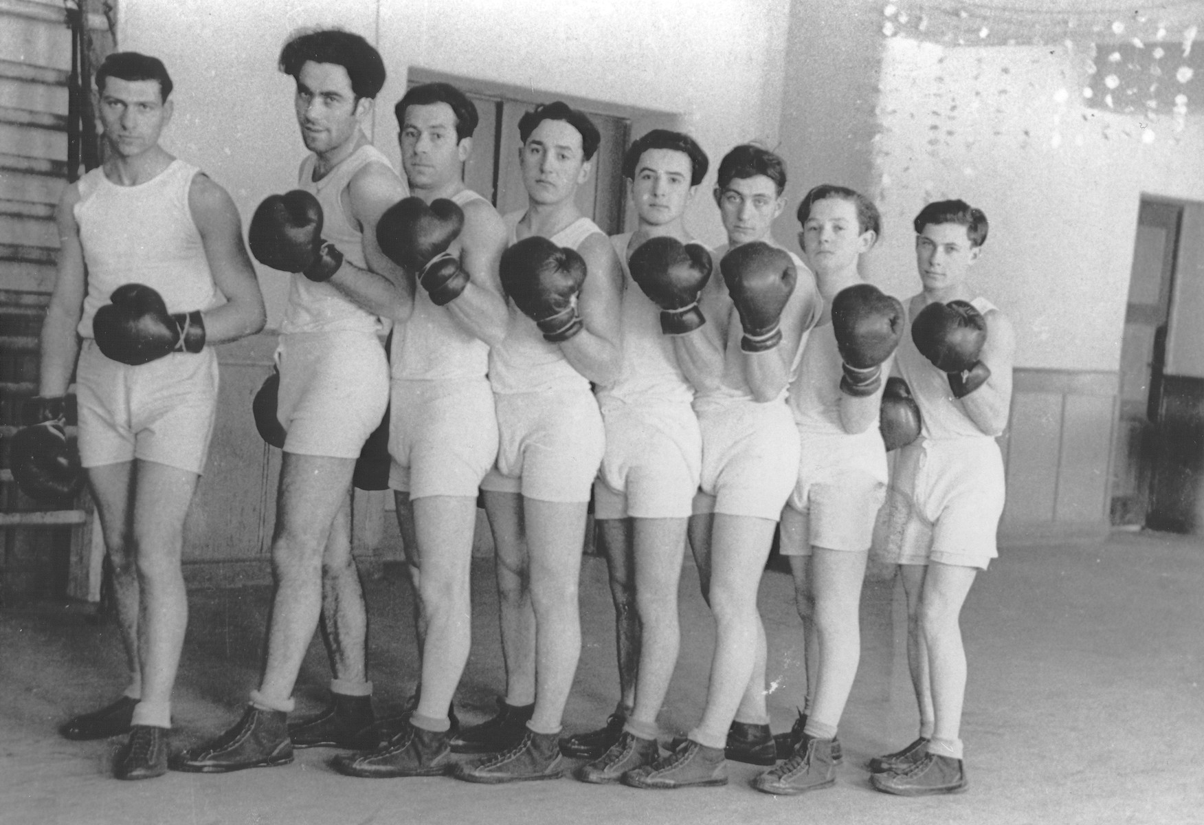 Group portrait of members of a Jewish boxing team at a displaced persons camp in Germany [probably Hofgeismar].  Standing third from the left is Majzesz Szczukowski.