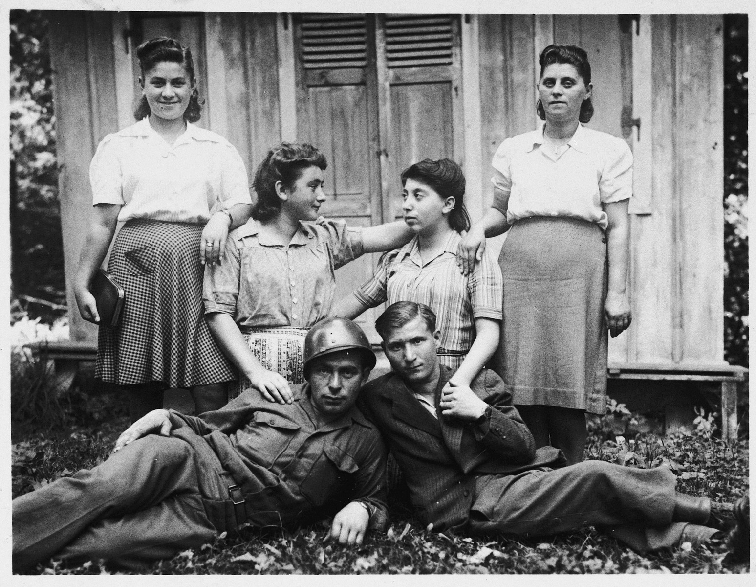 Six Jewish DPs pose outside a wooden barracks in the Feldafing displaced persons camp.  Among those pictured is Minia Wasilkowska (second from the right).