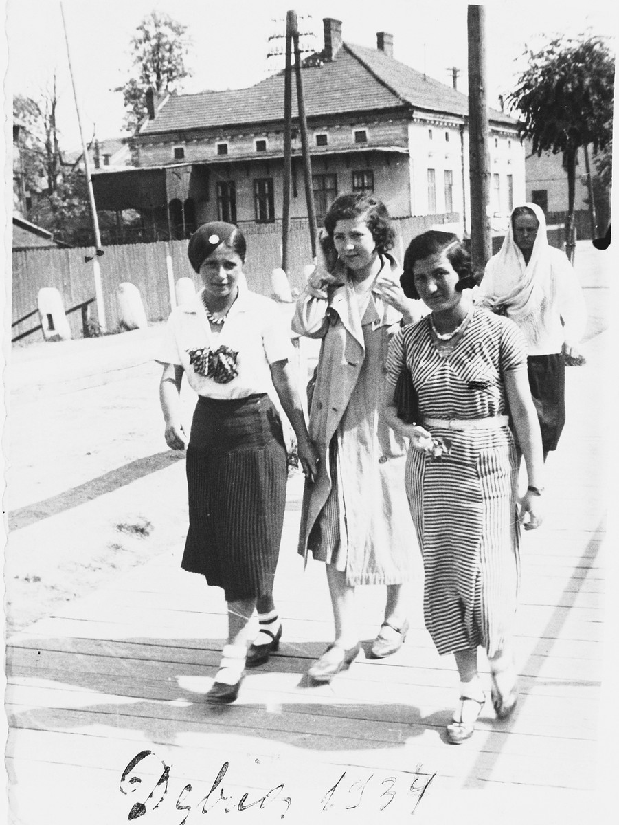 Three young Jewish women walk along a street in Debica, Poland.  Pictured from left to right are: Regina Hollender, Susi Hollender and Helena Fisz.