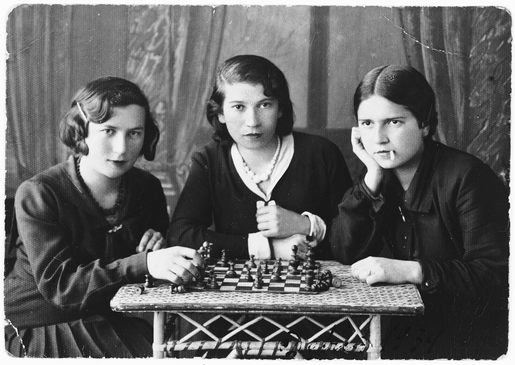 Studio portrait of three young women posing around a chessboard.  Pictured from left to right is: Frieda Fisz, an unidentified Polish schoolmate and Sara Hollander.