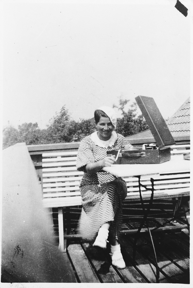 A young Jewish woman poses with a phonograph while on vacation on the Oresund in Faxe Ladeplads, Denmart,  Pictured is Kaja Diament.