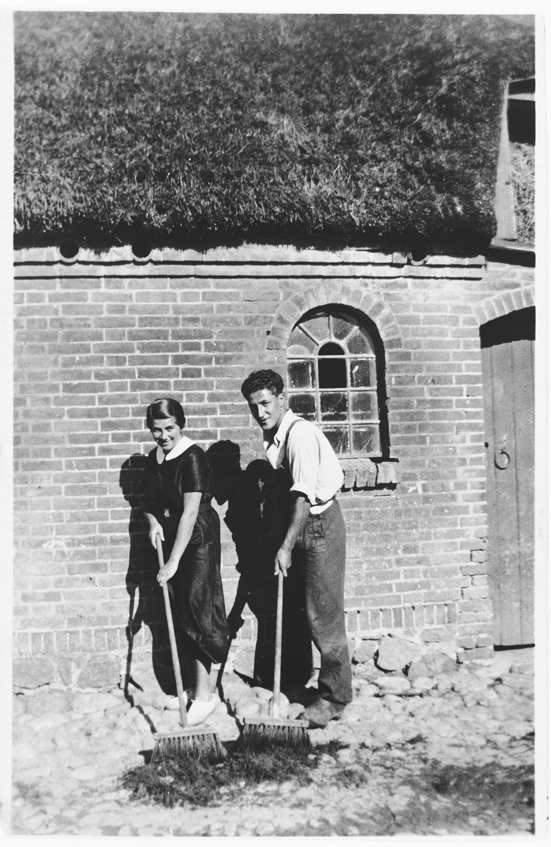 A young Jewish refugee from Germany sweeps outside with his girlfriend on a farm in the Jutland, where members of his hachshara [Zionist collective] are living.  Pictured are Josef Geldmann and Kaja Diament.
