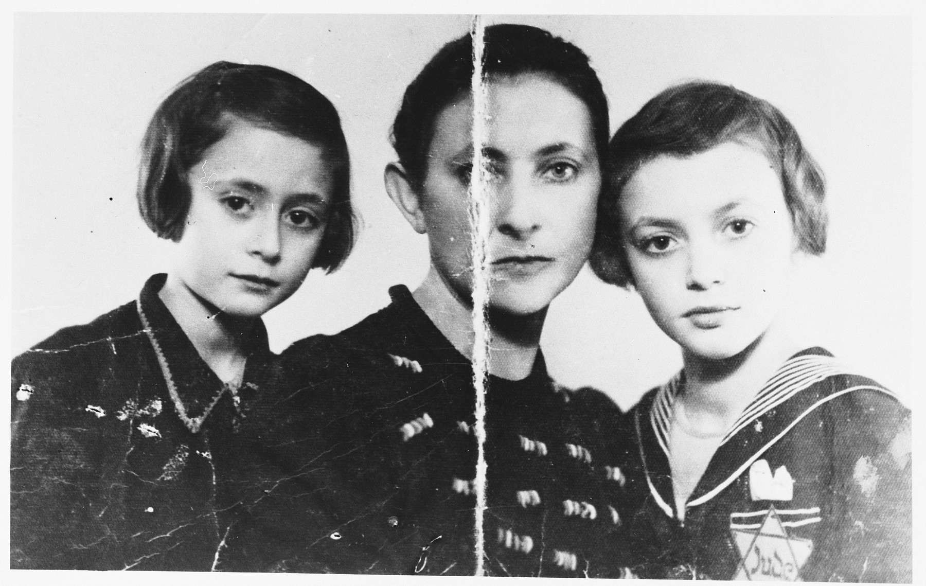 Studio portrait of a Jewish family in Jaworzno in German-occupied Poland.  Pictured are Esther (Halman) Hirschberg and her two daughters. Leah Hirschberg is pictured on the right wearing a Jewish badge.  The photo was taken shortly before they were deported to Auschwitz where they were killed by the Germans.  Esther's husband, Mailoch Hirschberg, kept the photograph folded in two and hidden in his shoe until the end of the war.  Esther was the youngest sister of Felicja (Halman) Lieberfreund.
