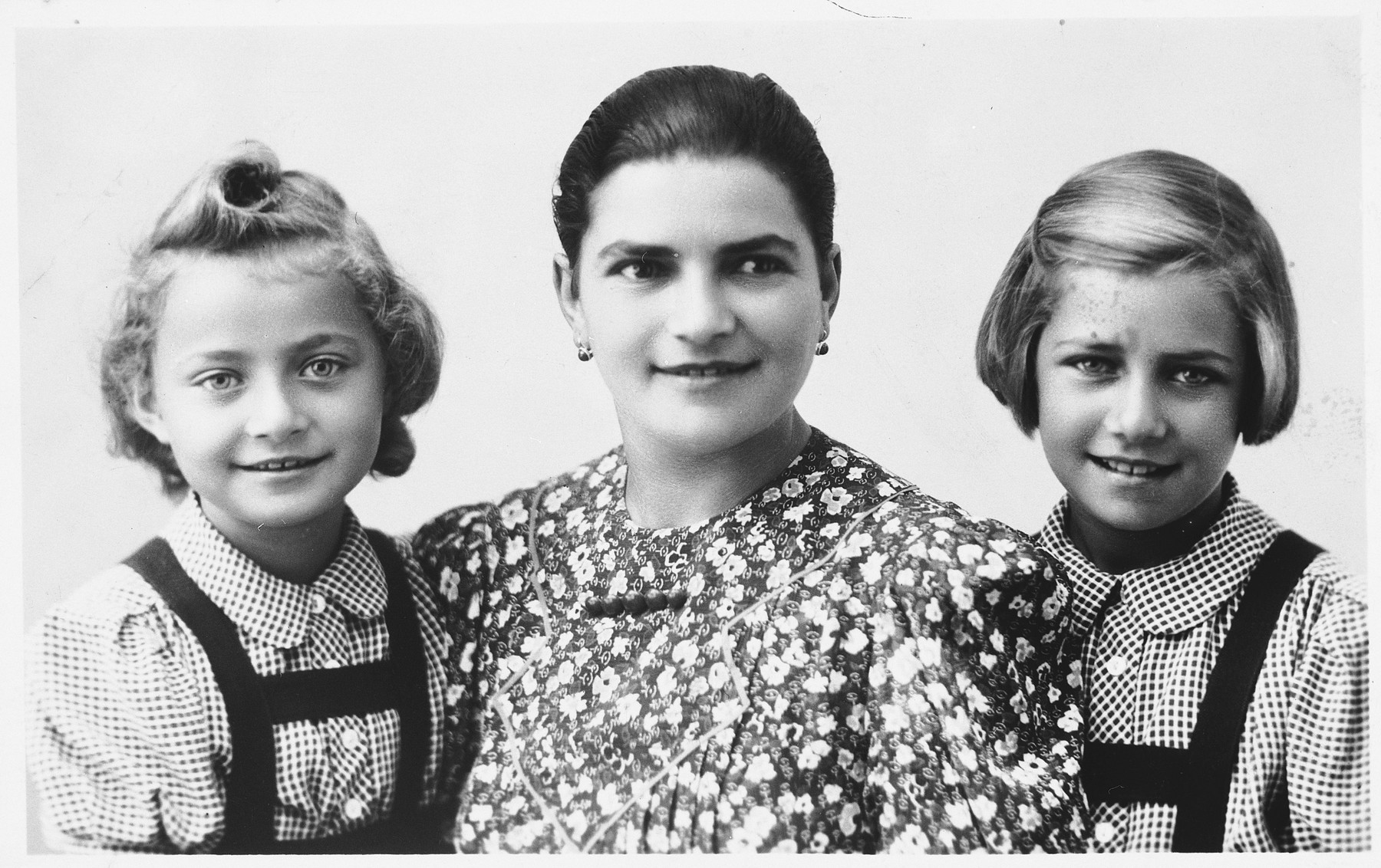 Studio portrait of a Jewish mother and her two children in Holice, Czechoslovakia.  Pictured are Etelka (Meisels) Frei and her two daughters, Gabriella and Katerina.