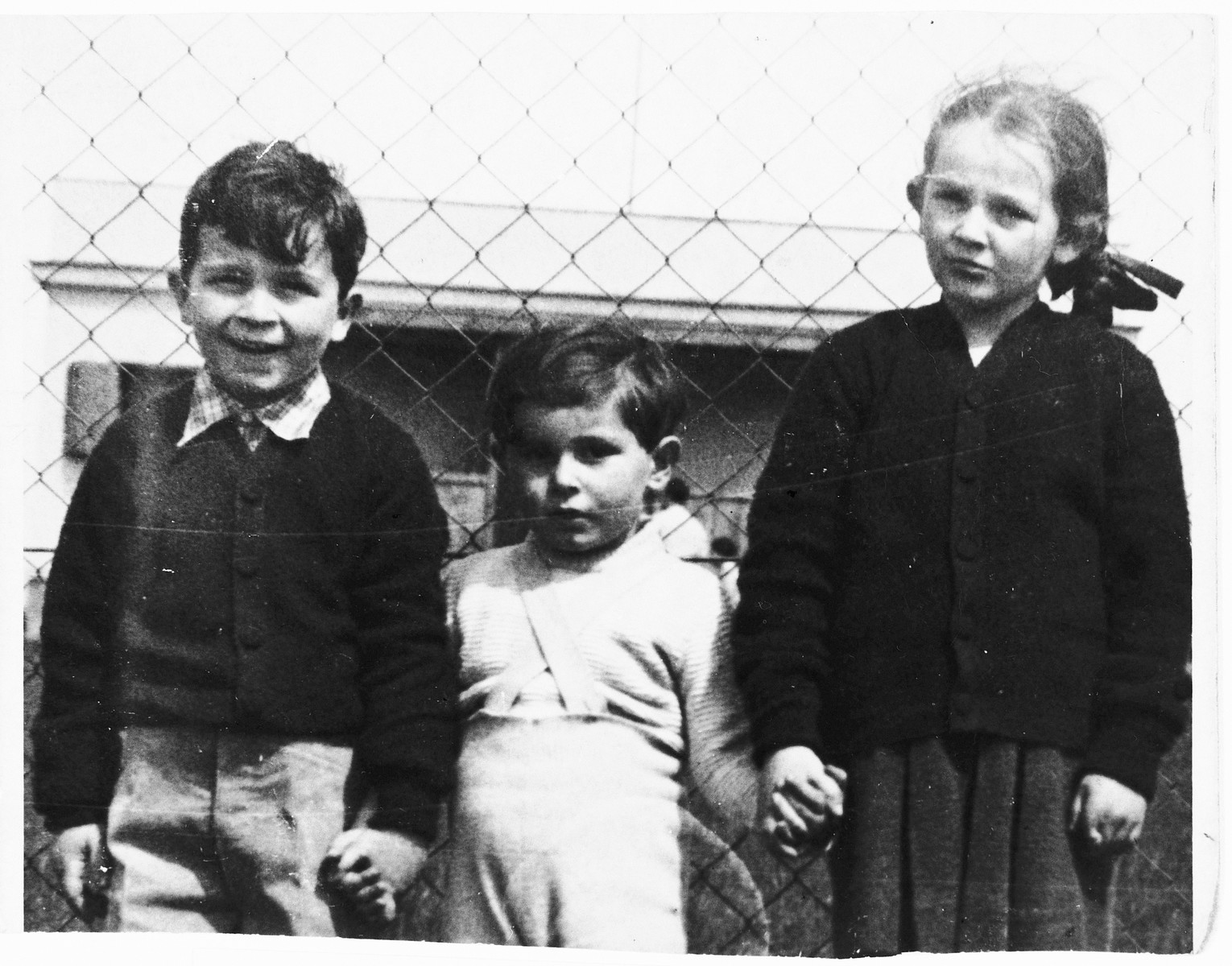 "Three Czech Jewish children pose outside in front of a chain-link fence.  Pictured are Nina and Peter Lederer flanking their cousin Ivan Rechts.  Both perished in Auschwitz.  One of Nina's drawings from Theresienstadt appears in ""I Never Saw Another Butterfly."""