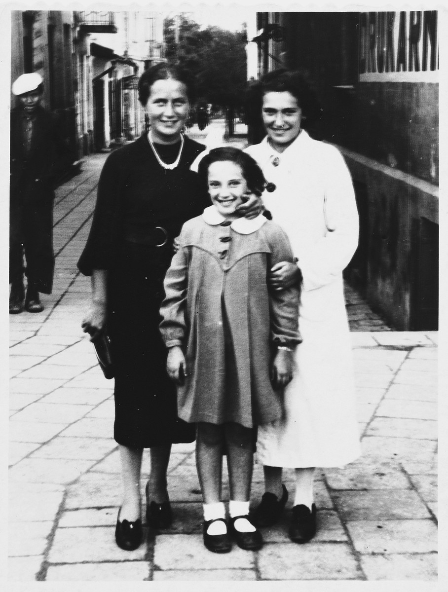Frieda Fisz (left) poses with a Jewish friend and her daughter on a street in Debica, Poland.
