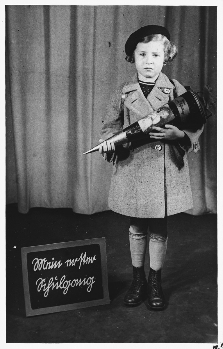 """Portrait of a young girl in Berlin holding a Schultuette (school cone) next to a sign that reads, """"My first day of school.""""   Pictured is Brigitte Joseph."""