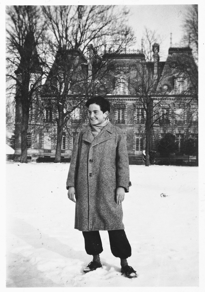 A Jewish refugee youth poses outside in the snow in front of the Chateau Quincy-sur-Senart children's home.  Pictured is Eryk Goldfarb.