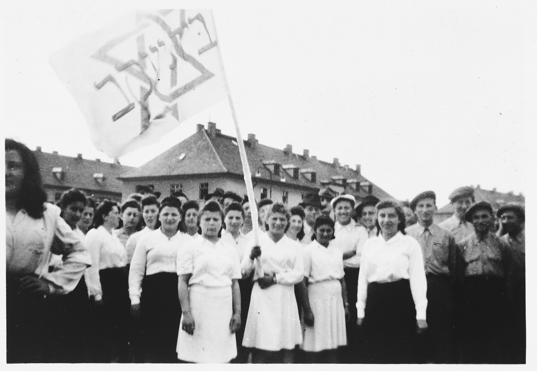 Teenagers from the Beit Yaakov religious school for girls, wave a flag during a Zionist demonstration in the Bergen-Belsen displaced persons camp.