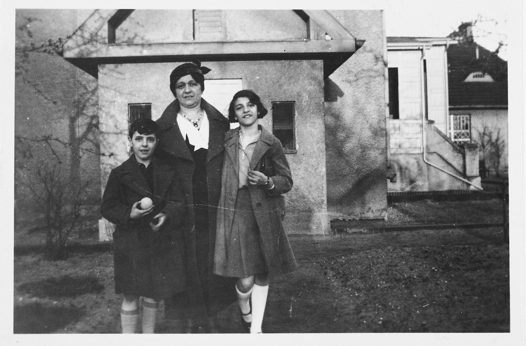 A Jewish mother and her two children pose outside an old age home in Germany.  Pictured from left to right are: Heinz, Ella and Alice Redlich.