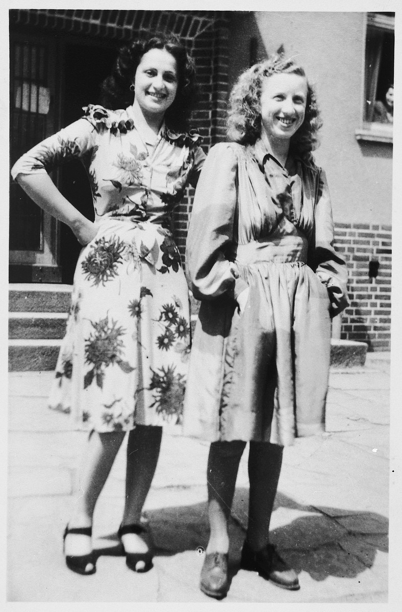 Two sisters pose outside the L1 building in the Bergen-Belsen displaced persons camp.  Pictured are Olga Schwartz (left), who became an administrator of a kibbutz hachshara [Zionist collective] and Esther Schwartz (right), an administrator for the Beit Yaakov school in the camp.