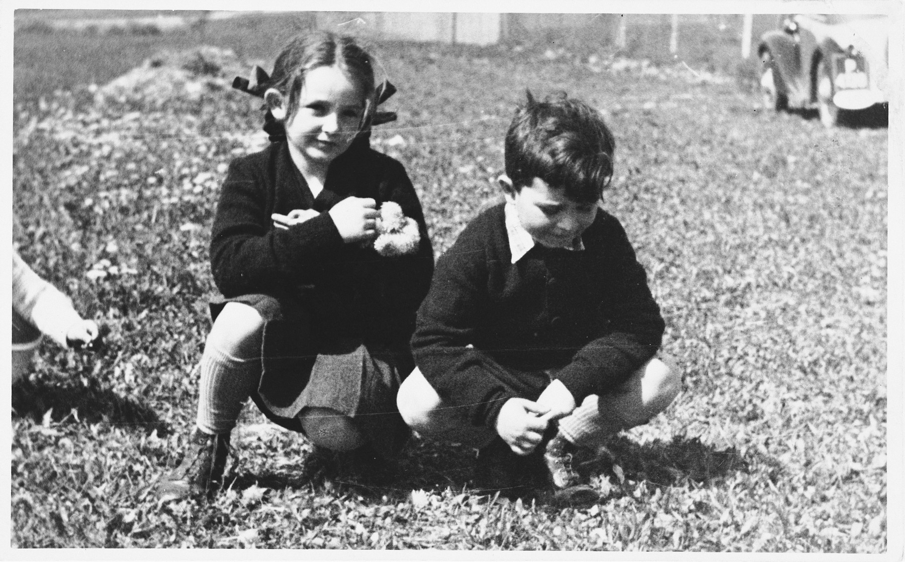 "Two Czech Jewish children pose outside in a grassy field.  Pictured are the siblings, Nina and Peter Lederer.  Both children perished in Auschwitz.  One of Nina's drawings from Theresienstadt appears in ""I Never Saw Another Butterfly."""