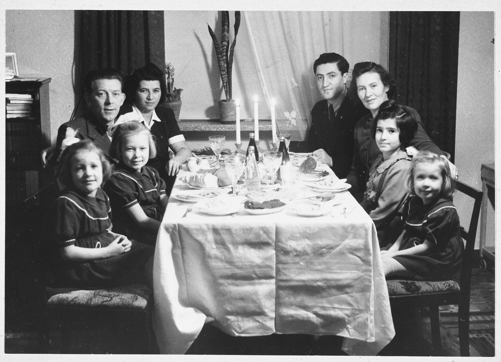 A Jewish family from Denmark who was ferried to safety in Sweden, has Christmas dinner at the home a Swedish family in Landskrona.  Pictured clockwise from the bottom left are: Johanson child, Gunn Johanson, Mr. Johanson, Kaja Geldmann, Josef Geldmann, Mrs. Johanson, Birthie Geldmann and Johanson child.  The Johanson family provided the Geldmanns with clothing and toys after their arrival in Landskrona.  Gunn Johanson was a classmate and friend of Birthie Geldmann at the Topaskolen (school).