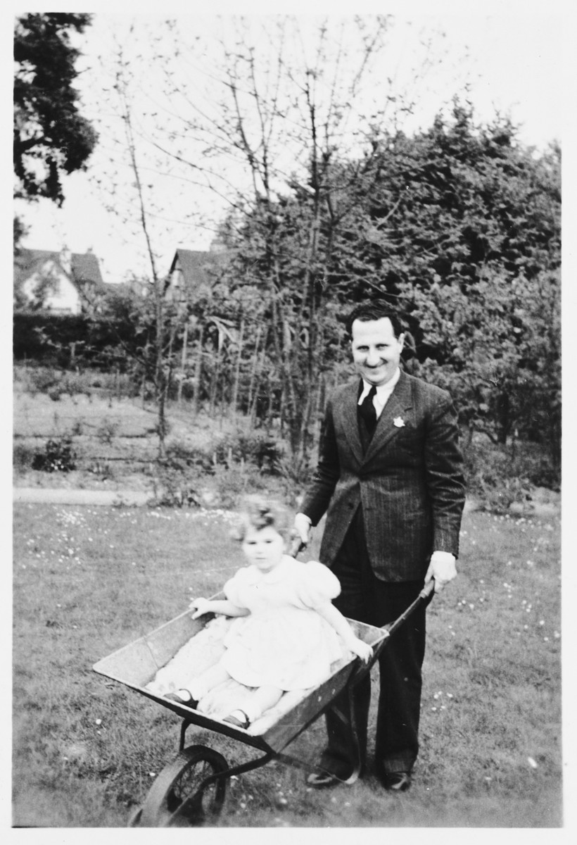 Bruno Foa pushes his daughter Eleanor in a wheelbarrow.