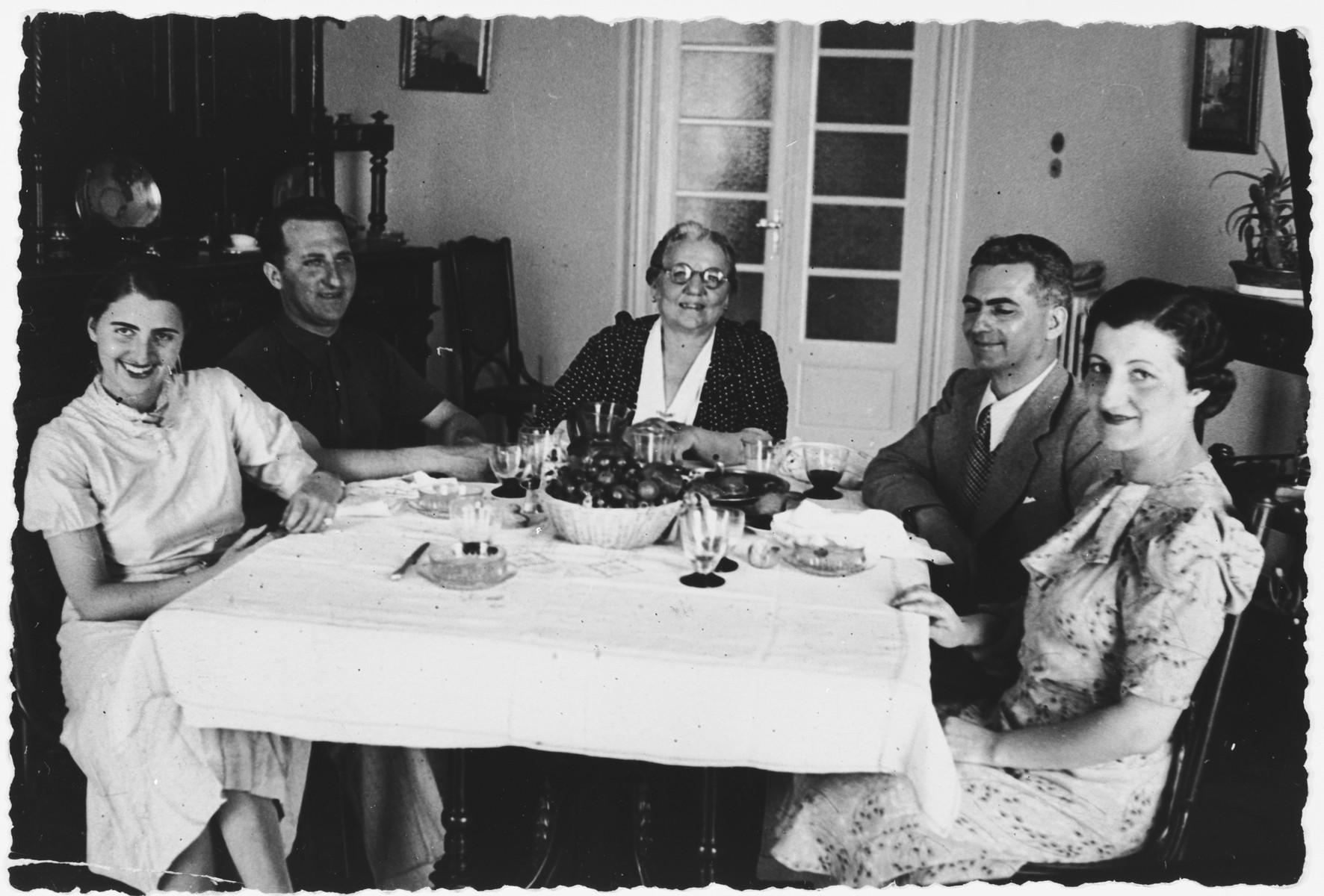 The Foa family gathers around the dinner table.  From left to right are Lisa and Bruno Foa, Grandmother Eleonora Foa, Joe Levi and his wife Marina Foa Levi.