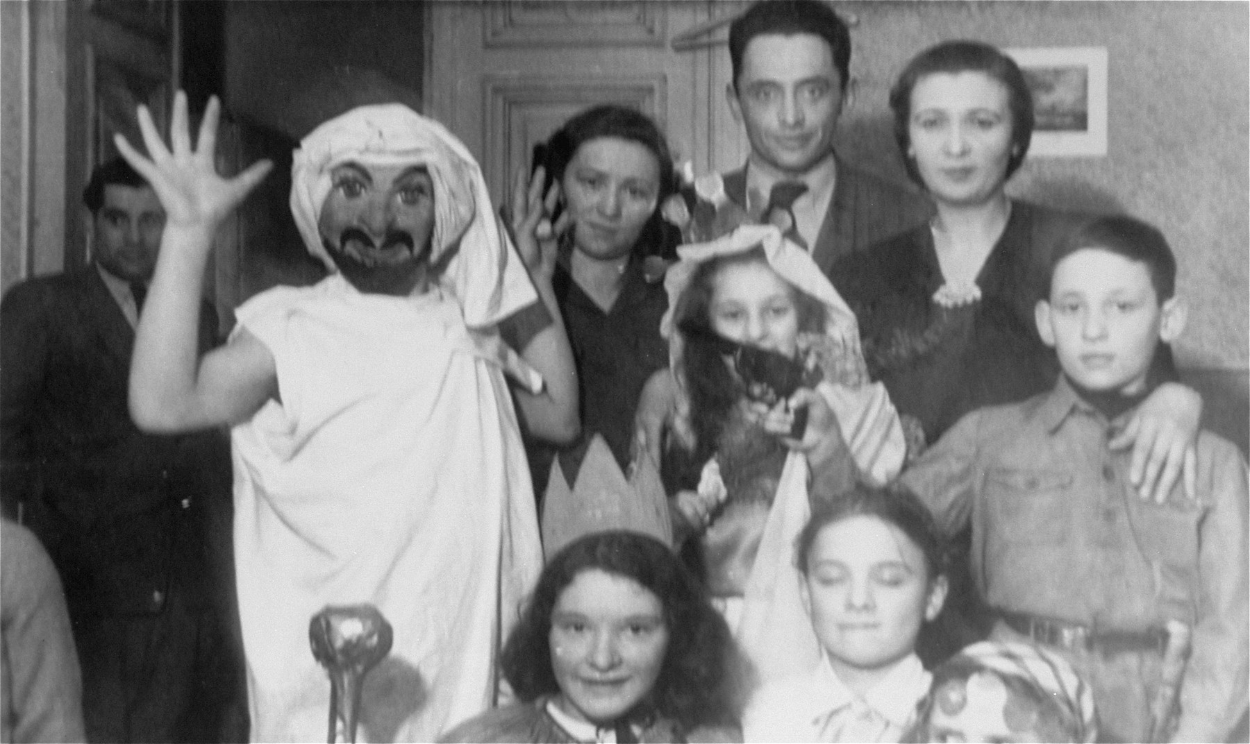 Purim celebration at an orphanage for Jewish children in Lodz run by the Koordynacja (Coordination Committee).   All of the children at the home had been hidden by Christian families during the war. The adults pictured in the rear are (left to right): Mrs. Zuza, Jehuda Bornstein, and Genia Distenfeld, secretary of the Koordynacja.