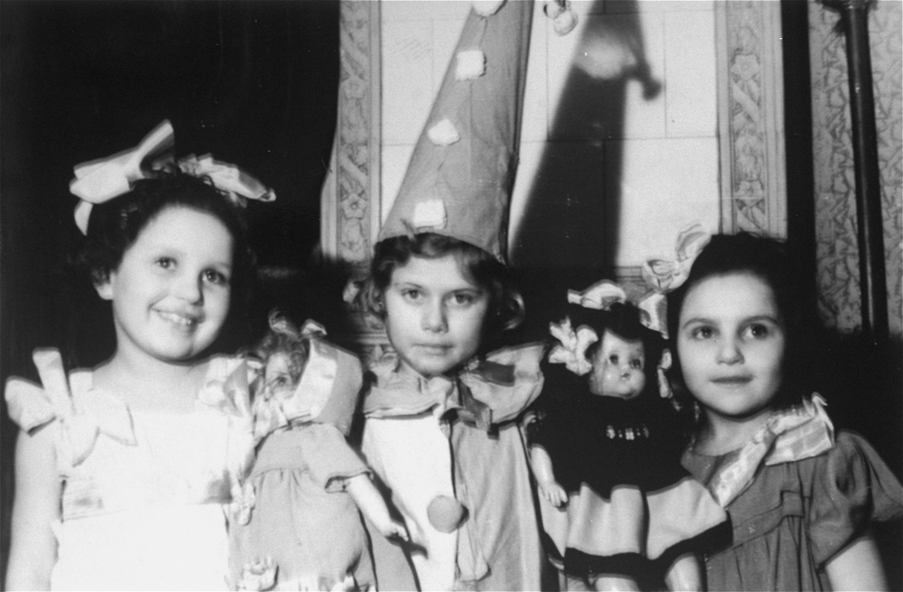 Hanukkah celebration at an orphanage for Jewish children in Lodz run by the Koordynacja (Coordination Committee).   All of the children at the home had been hidden by Christian families during the war. Pictured from left to right are: Basia David, Sabina (Inka) Kagan, and Renia. Basia had been hidden in Orlovo by the Polubinska family. Inka had been hidden by the Roztropowicz family in Nidzica.