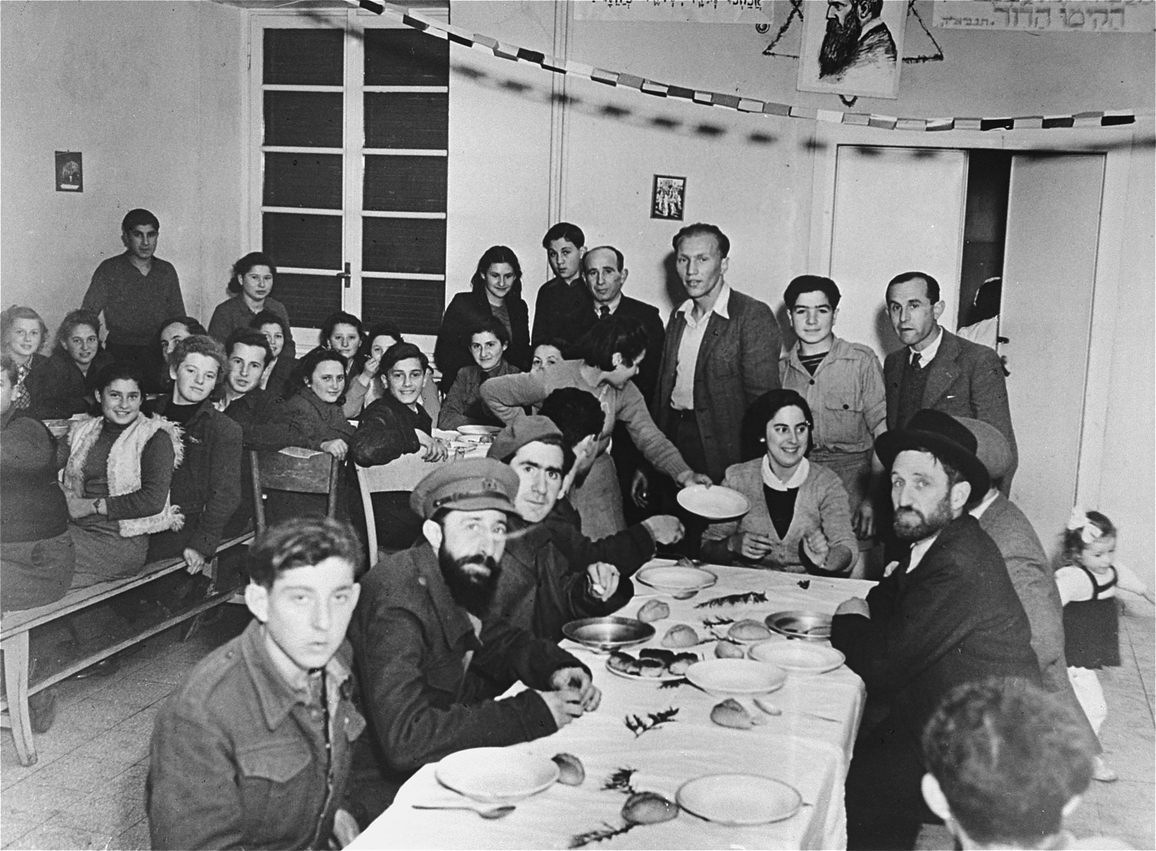 Teenagers and guests enjoy a festive meal at the Youth Aliyah children's home in Selvino, Italy.  Among those pictured are Shlomo Weisbrod, Noga Donat, Jeshayahu Flamholz, Isak Rechtman, Yaakov Meriash, Avraham Hassman, Helenka Saban, Lea Shnee, Miriam Weinstock, Yaffa Yanover, Edzia Winkler, Halina Liebeskind, Dora Rot, Yaakov Kopelman, Zvi Kaner, Zipora (Baranek) Friedman, Serka Fiederer.