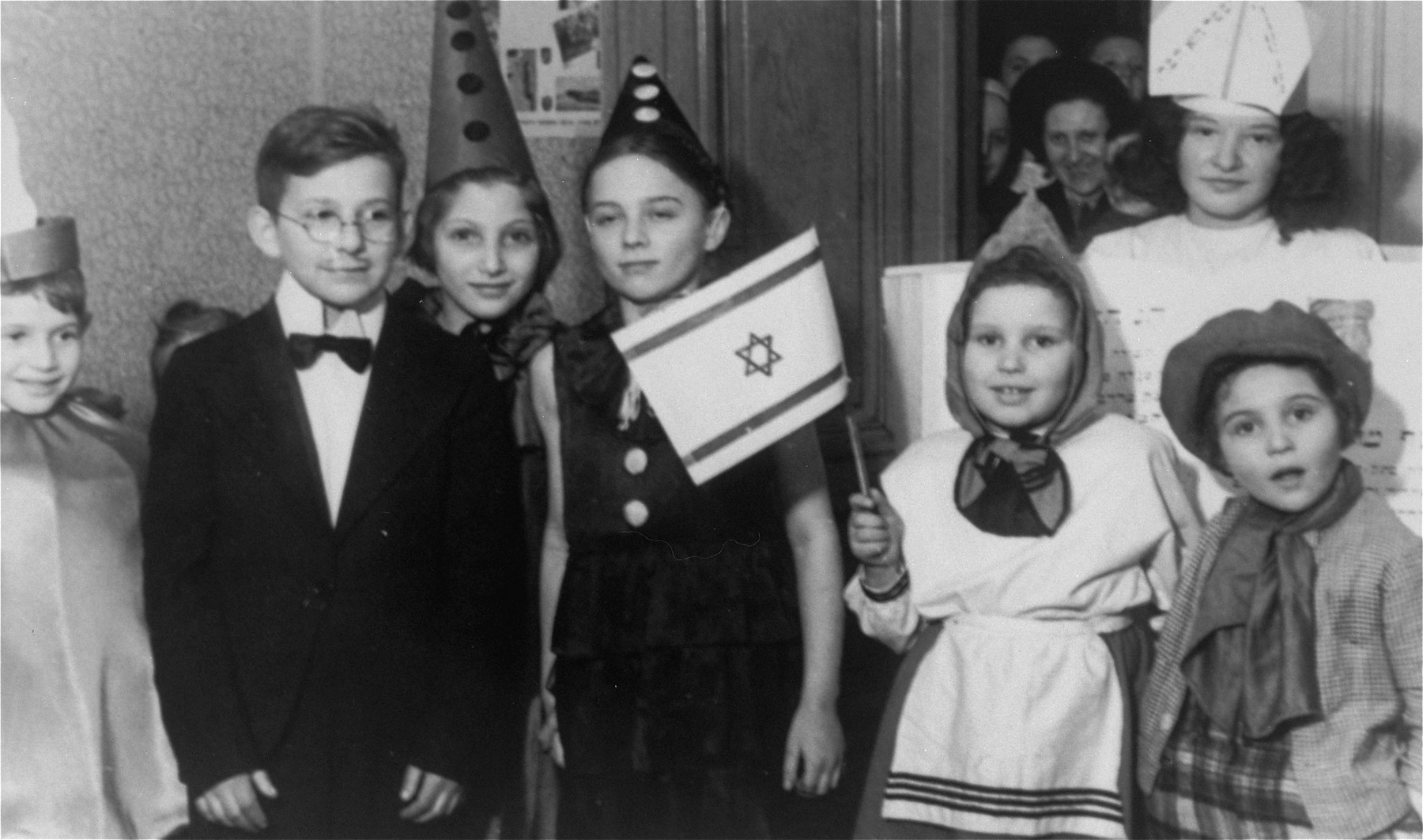 Purim celebration for Jewish children at an orphanage in Lodz run by the Koordynacja (Coordination Committee).   All of the children at the home had been hidden by Christian families during the war.  Pictured from left to right are: unknown, Leon, unknown, Nania Susel, Basia, Renia, and Rela (behind on the right).