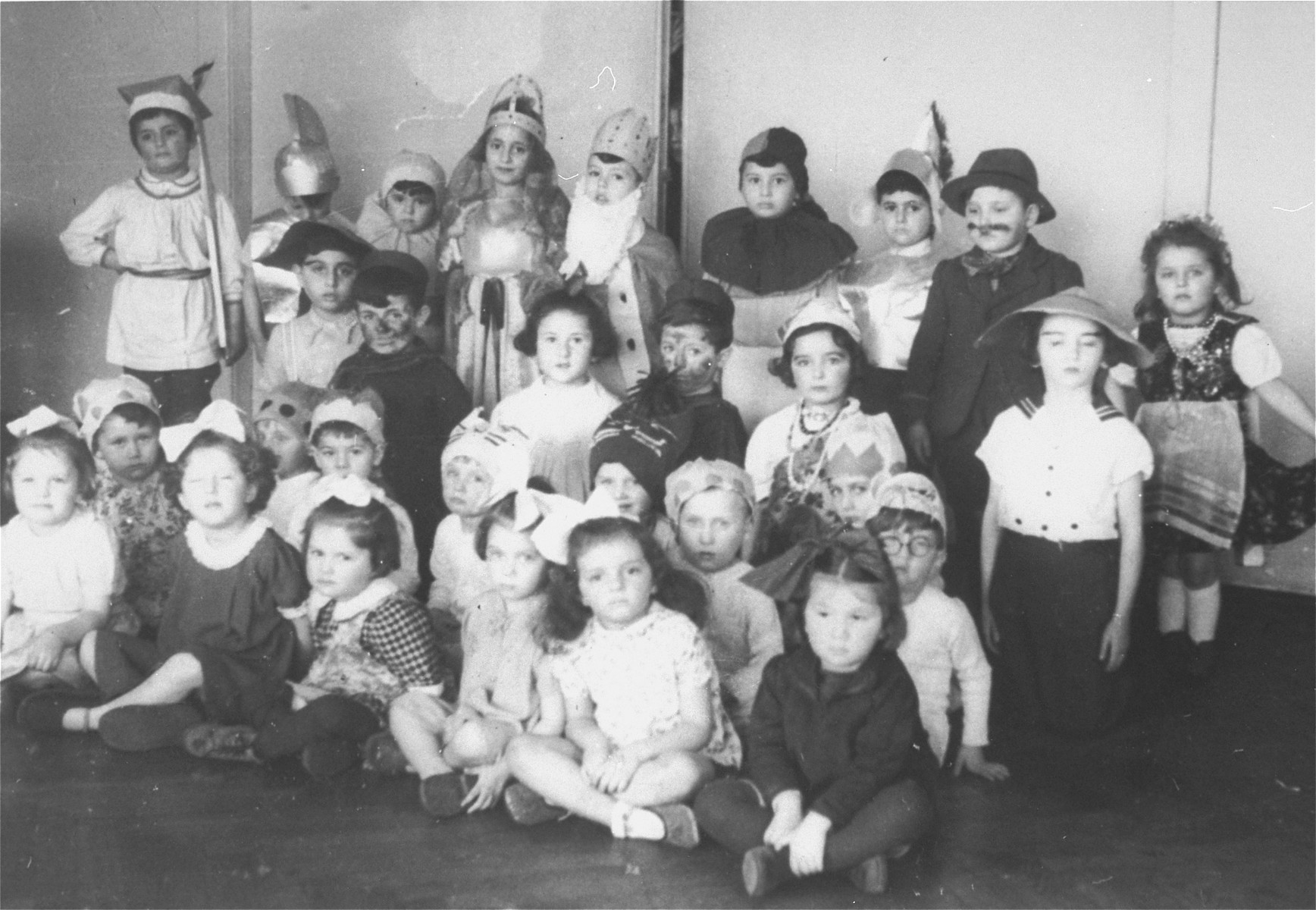 Group portrait of children dressed in costumes for Purim at a Jewish children's home in Krakow.  Among those pictured is Jehudit Joffe (now Monica Goldner).  Jehudit, who was hidden during the war, was brought to a children's home in Krakow after the liberation.  She lived in the home for a year and a half before she was adopted.