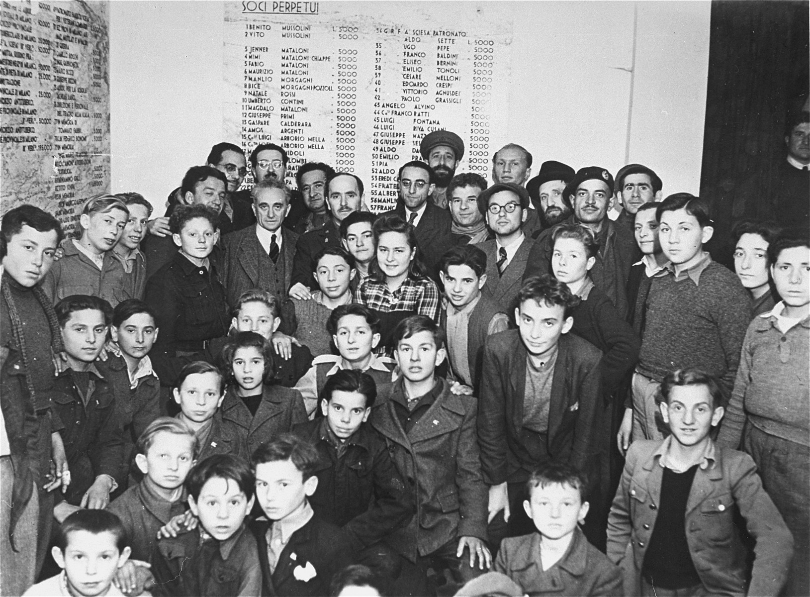 Group portrait of the staff and children of the Youth Aliyah children's home in Selvino, Italy.  The names on the wall are Italian donors who paid for Mussolini to build the villa as a Fascist youth center.  Among those pictured are Izak Abramowitz, Yaakov Meriash, Avraham Lipkunski, Jeshayahu Flamholz, Anita Teitelbaum, Moshe Blumenstock, Leon Lindenbaum, Matitiahu Drobles, Chaim Abramowitz, Surkis, Moshe Zeiri, Israel Drobles, Alpert, and Szlama Fachter.