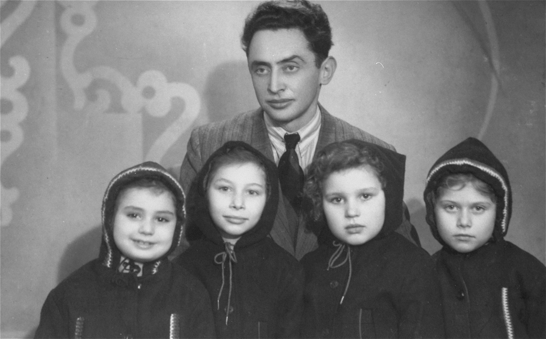 Jehuda Bornstein poses with four Jewish girls he retrieved from hiding and placed in a children's home on Narutowicza Street in Lodz.   Pictured from left to right are: Halinka, who was hidden as Zinaida Bar in Legnica, Poland by a Christian woman whose name was Ostrowska; Wandeczka, now known as Tamy Lavee, who had been hidden by a Christian woman; Basia David, who was hidden in Orlovo by the Polubinska family who treated Basia so well that she didn't want to leave them; and Sabina (Inka) Kagan, hidden by the Roztropowicz family in Nidzica.