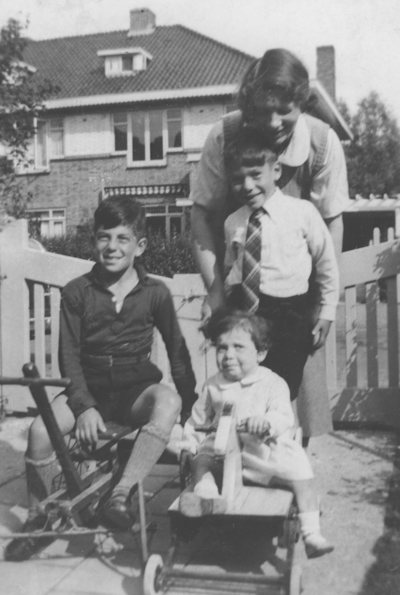 A mother plays with her three children in the yard of their home in Heemstede, Holland.  Pictured are Friederike, Paul, Rudi and Eve Oppenheimer.