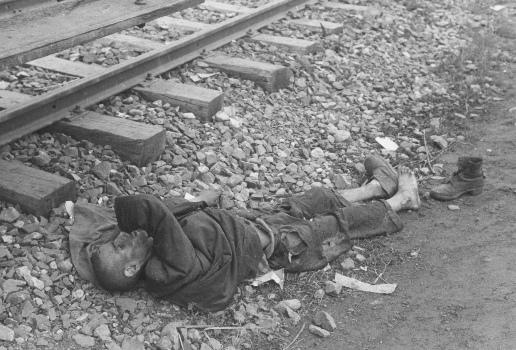 The corpse of a prisoner lies next to the train tracks in Dachau.