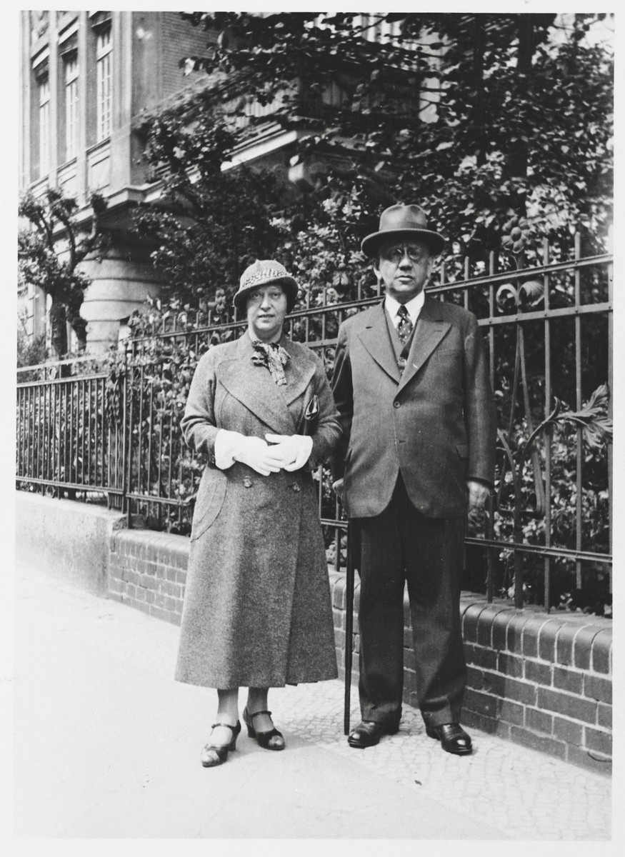 Louis and Margarethe Wilhelm pose on a sidewalk next to a rod iron fence.    Louis and Margarethe Wilhelm were the parents of Annie Witting.  Louis Wilhelm was a wholesale wheat merchant with a seat on the Wheat Exchange in Berlin.  He died of natural causes on March 23, 1941.  After his death, Margarethe went into hiding.  She eventually committed suicide on November 15, 1943 at the age of 61.