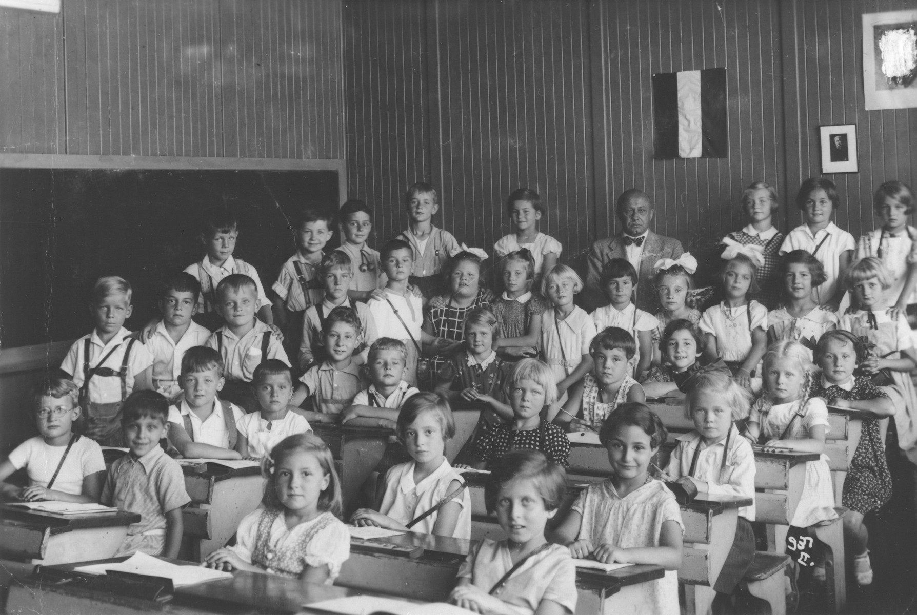 Children sit at their desks in a school in the Templehof neighborhood of Berlin.  Among those pictured is Paul Oppenheimer (third row, second from the left), the only Jewish child in the school.  A portrait of Hitler hanging on the wall was later rubbed out by the donor.