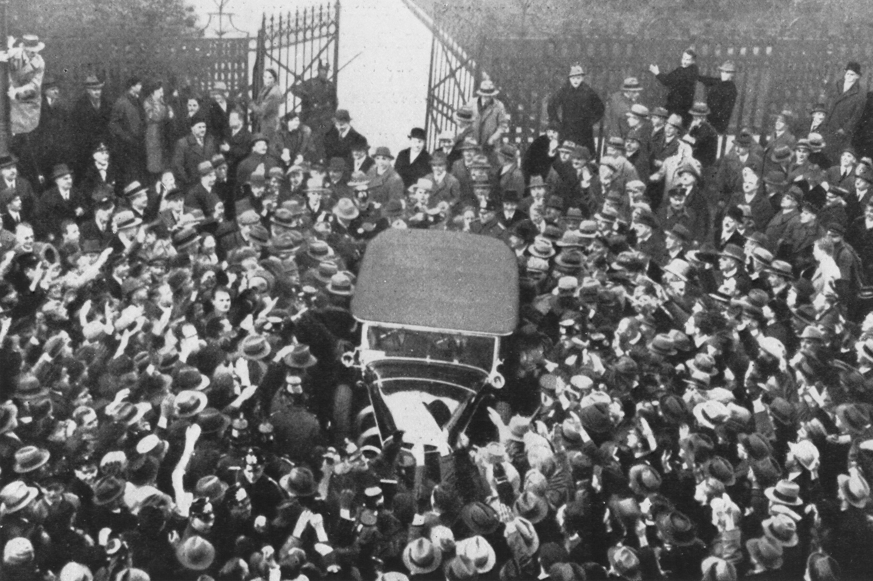 An automobile in which Adolf Hitler is riding moves through a crowd of supporters as it leaves the Chancellery after Hitler's meeting with President Paul von Hindenburg.