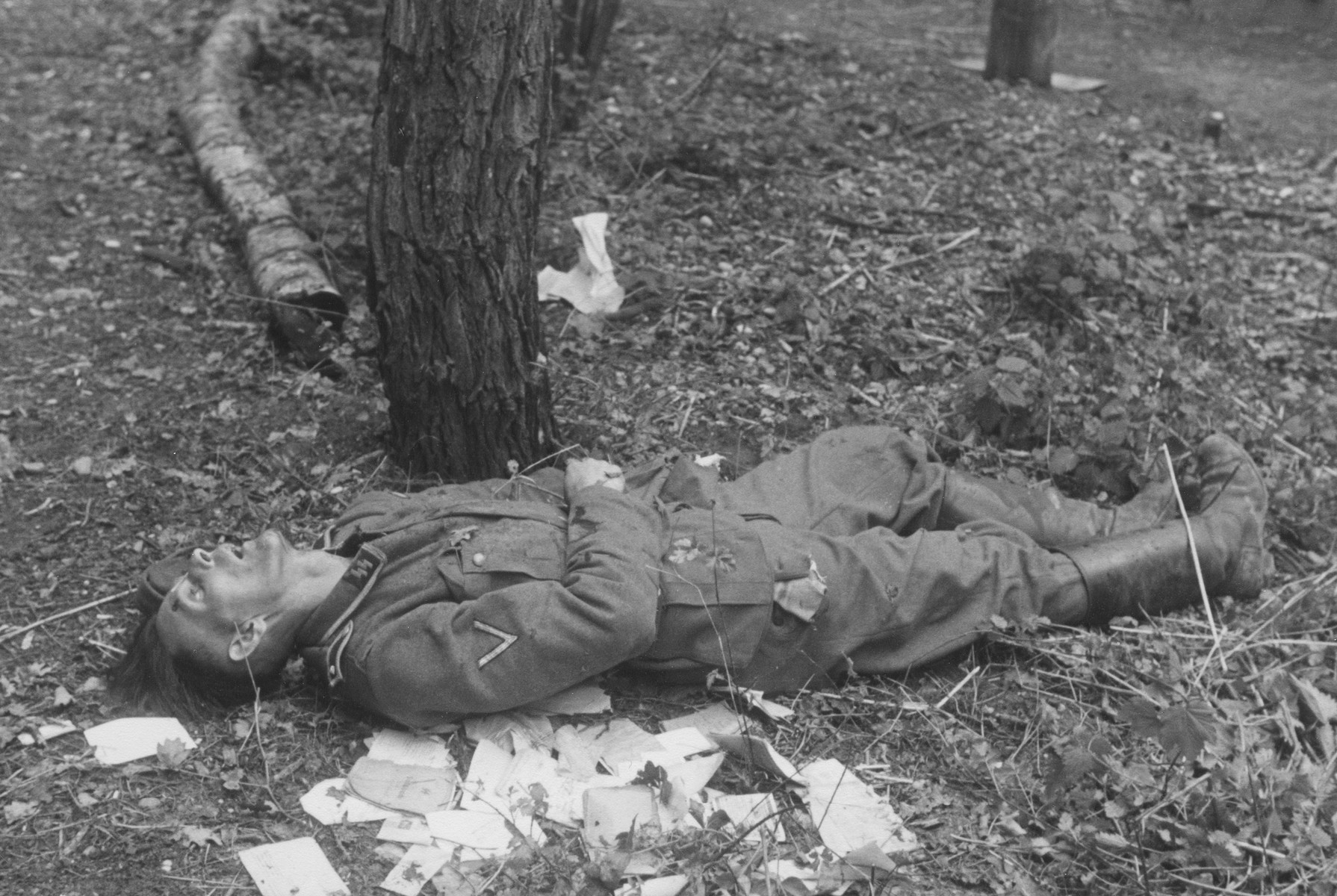 A slain camp guard lies in the grass surrounded by what are probably his personal papers and documents.