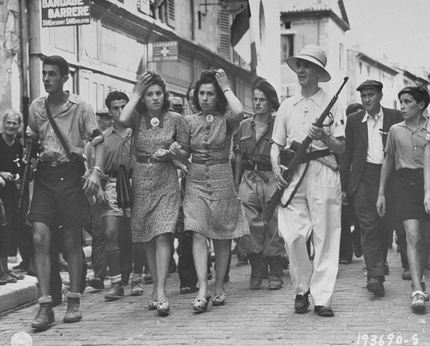 Members of the French resistance lead two women accused of being German sympathizers to the local prison, where their heads will be shaved as punishment for collaboration.