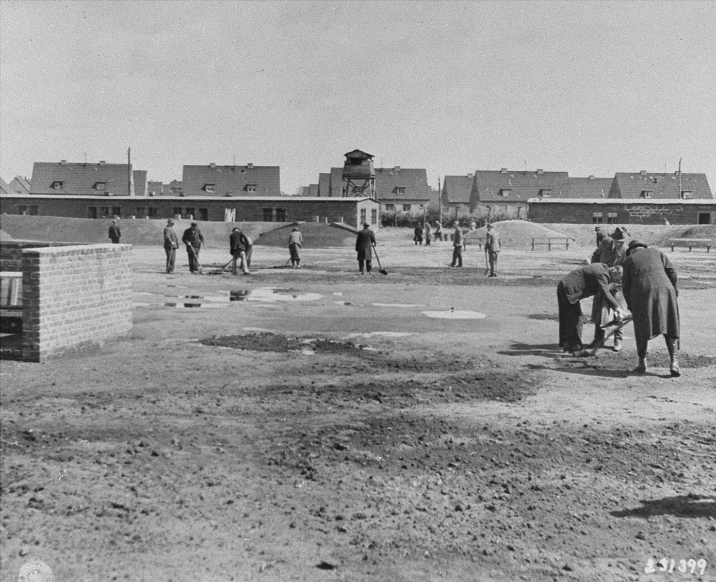 Germans incarcerated in the Recklinghausen internment camp fill puddles in the camp yard.