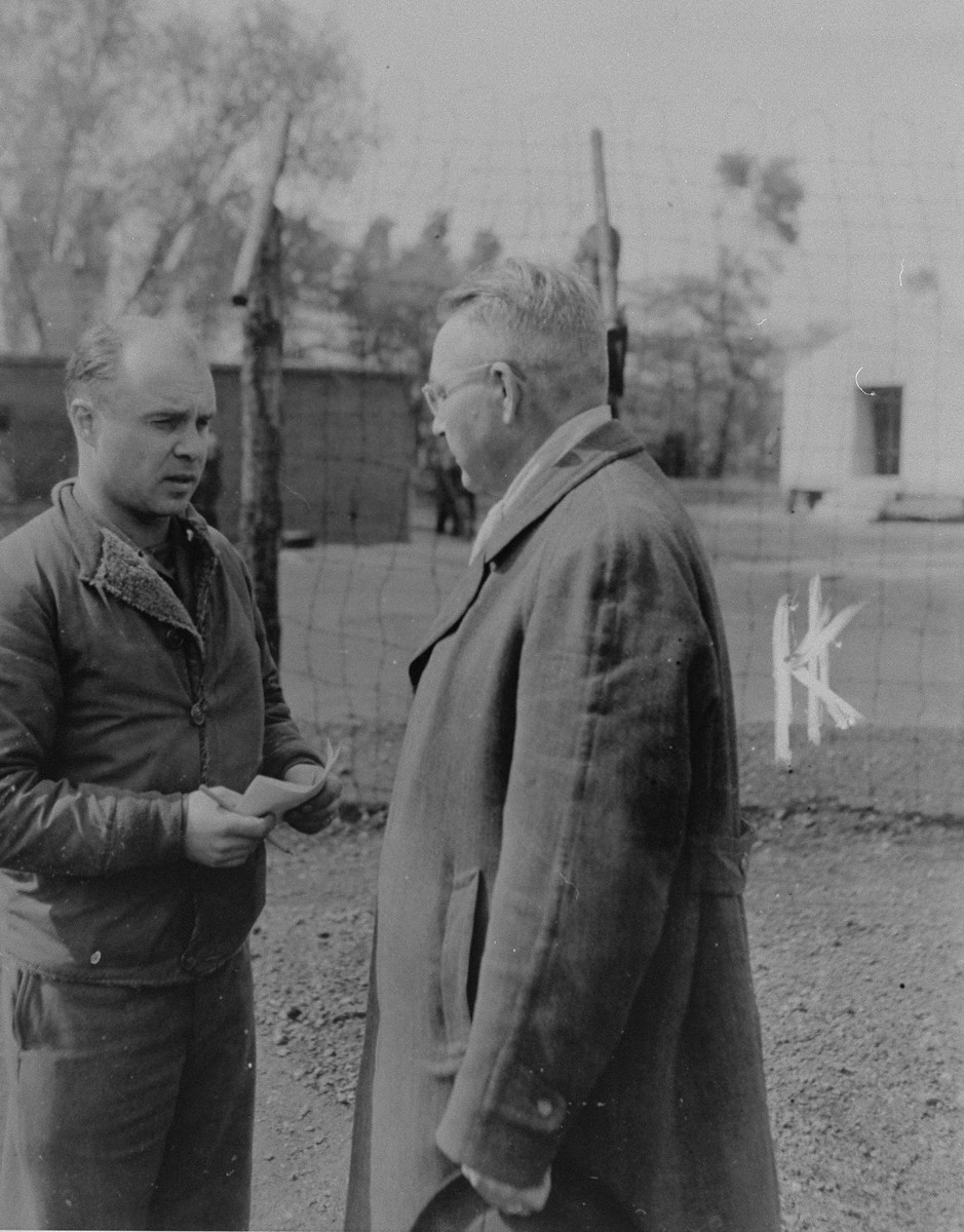 """An American investigator from the 79th Infantry Division, U.S. Ninth Army interrogates Dietrich Klagges (right), the former Minister President of Braunschweig and a Lieutenant General in the SS, during his incarceration in the Recklinghausen internment camp.  Klagges was in Recklinghausen while being investigated for his responsibility in the murder of captured American pilots and mistreatment of slave laborers.  When U.S. Ninth Army troops captured the concentration camp for Soviet civilians located near Recklinghausen, Germany, they converted it into a separation center for prisoners of war and war criminals.  After the first German prisoners arrived at the camp they were sent to the interrogation department, which was supervised by Captain Harold Puttfer and Lieutenant H. Goodman.  The camp had three sections called """"cages.""""  One of these was for women, another for persons incarcerated for minor offenses, and the third for hardened criminals.  All three sections were filled to capacity, totalling 20,000 prisoners."""