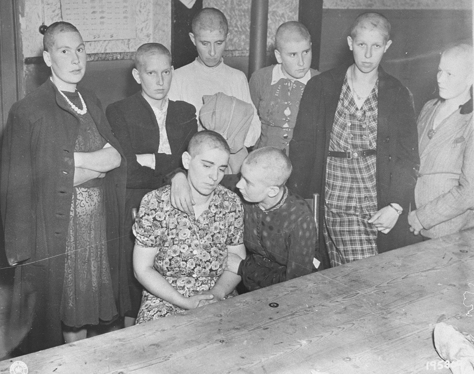 Women accused of collaborating with the Germans wait to be marched through the streets of Grave by the Dutch resistance.  The womens' heads were shaved in preparation for their public humiliation.
